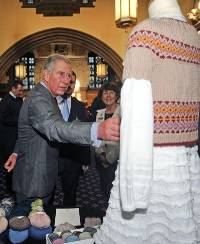 The Prince of Wales looks at wool products on display during his visit to promote the Campaign for Wool in Bradford