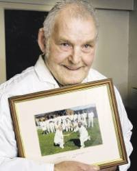 George Cowton, pictured holding a photo of the Cayton v West Indies teams who played a friendly game he umpired in 1999